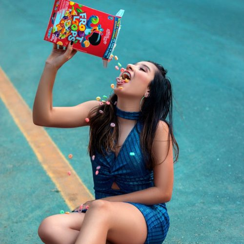 woman-sitting-on-the-road-eating-froot-loops-1805405